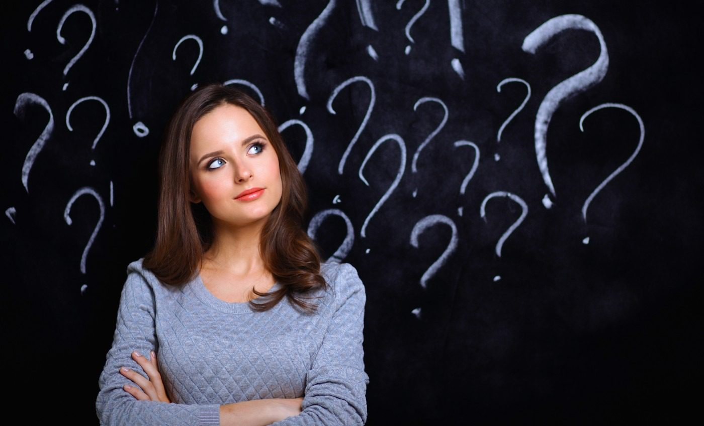 Lady with arms crossed in front of chalkboard with question marks